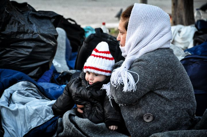 A Syrianrefugee holds her baby at the Souda refugee camp on the island of Chios on November 20, 2016.