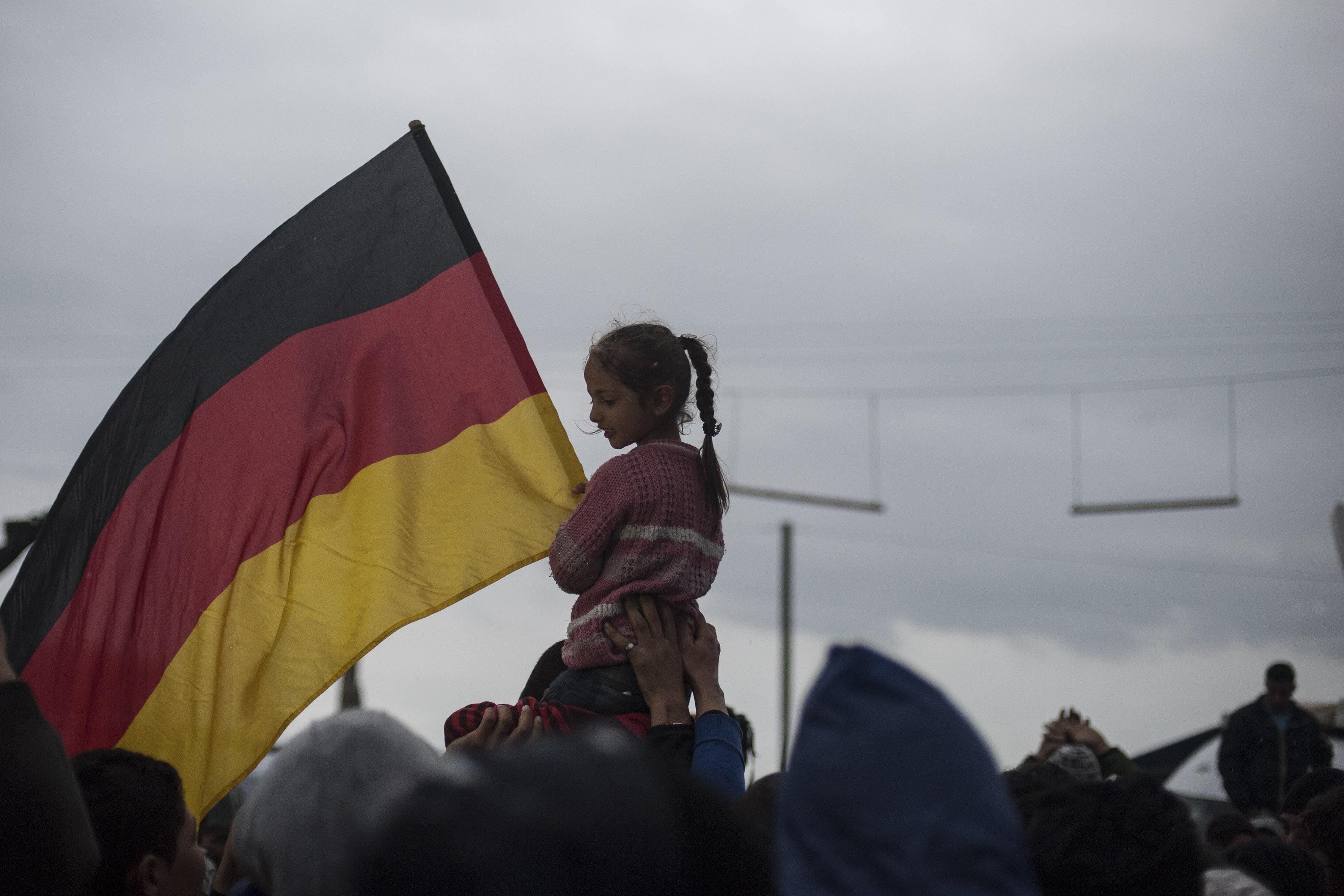 A child raises a German flag at a refugee camp.