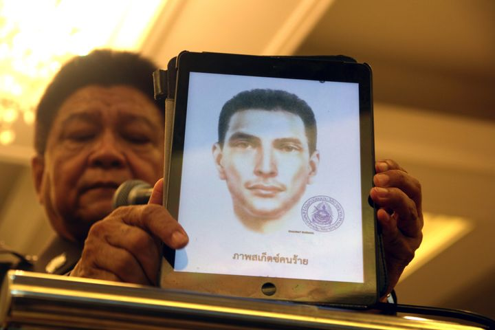 Thailand's national police spokesman Prawut Thavornsiri holds a tablet displaying a picture of an unnamed foreign man wanted