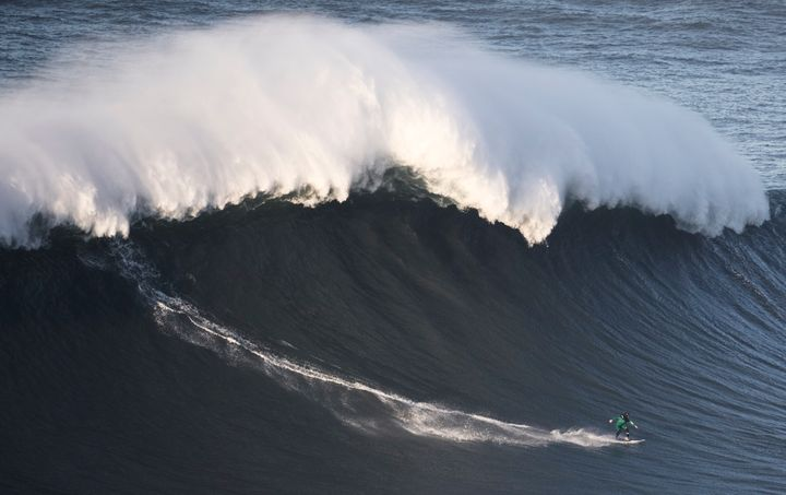 Andrew Cotton rides a wave during a December big wave competition at Praia do Norte in Nazare Portugal.
