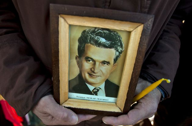 A man holds a framed picture of Romanian communist dictator Nicolae
