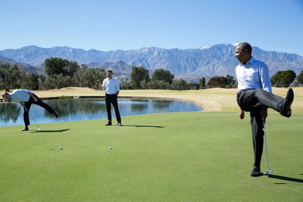 Obama reacts as his putt falls just short during an impromptu hole of golf with staffers Joe Paulsen, left, and Marvin Nichol