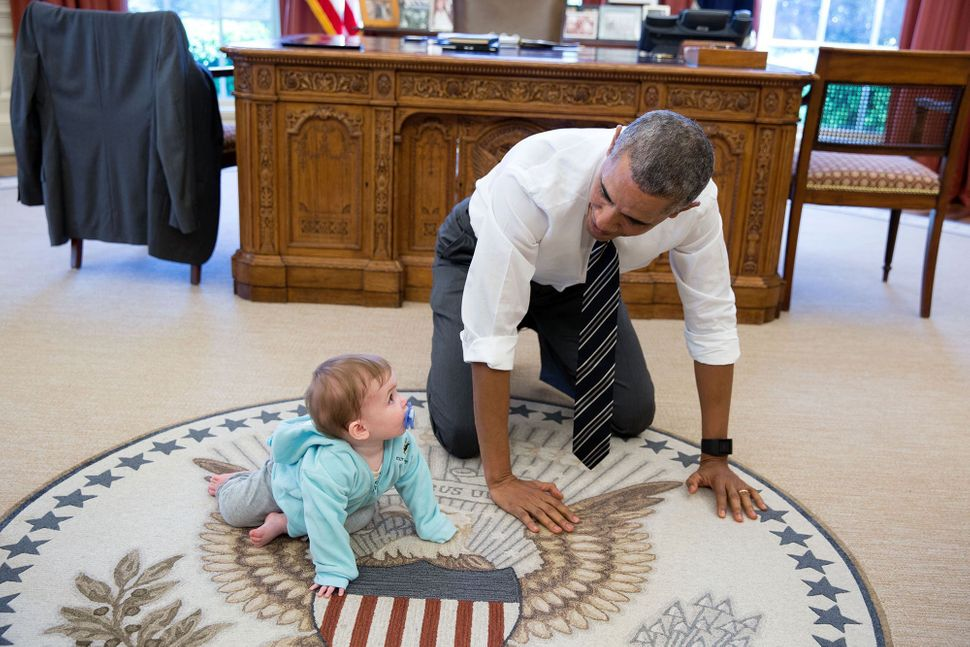 Obama crawls on the ground with Communications Director Jen Psaki's daughter Vivi on April 14.