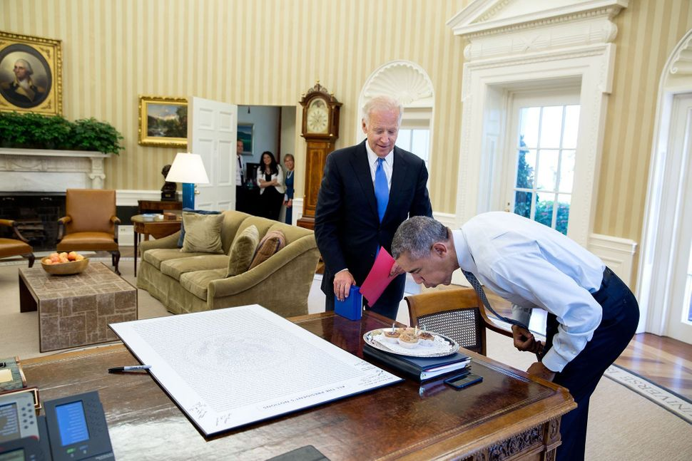 Obama blows out candles after Biden surprised him with some birthday cupcakes on Aug. 4.