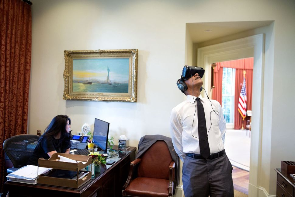 As Govashiri continues working, Obama watches a virtual reality film on Aug. 24 that was captured during his summer trip to Y