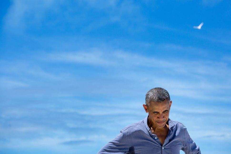 Obama pauses while talking with a writer from National Geographic during his Sept. 1 visit to Midway Atoll in the North