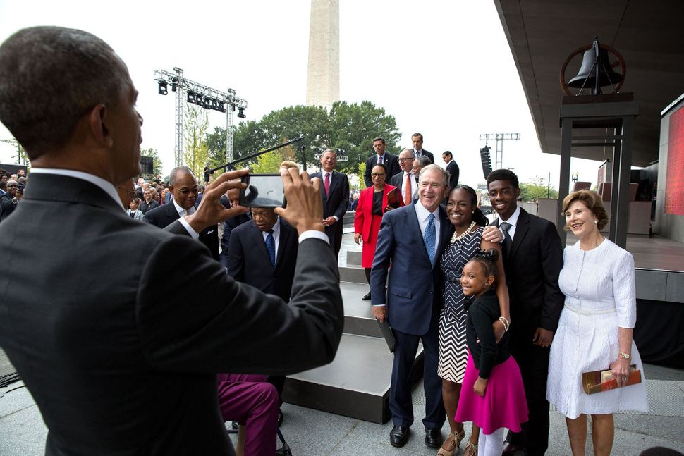 Obama snaps a photo of former President George W. Bush and former first lady Laura Bush with the Bonner family after the open