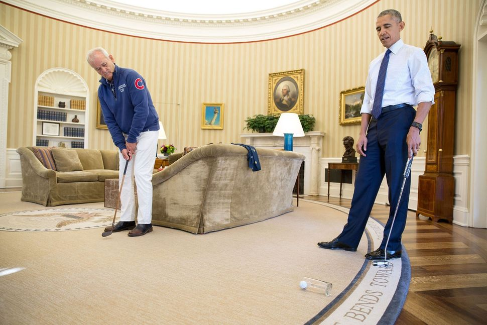 Actor Bill Murray putts into a glass in the Oval Office after stopping by to be honored as the recipient of the Mark Twain Pr