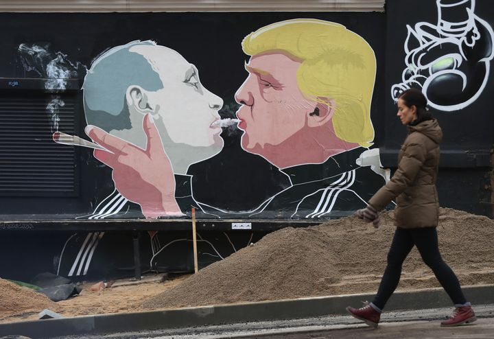 A woman walks past a mural showing President-elect Donald Trump (R) blowing marijuana smoke into the mouth of Russian Preside