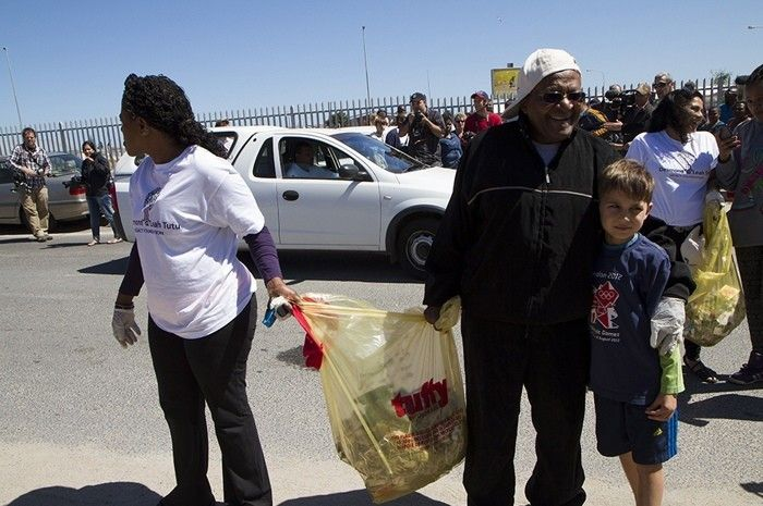 <em>Reverend Canon Mpho Tutu and the Archbishop are joined by young people to collect trash in one of the townships outside o