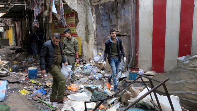 Iraqi security forces gather at the site of a bomb attack at a market in central Baghdad, Iraq December...