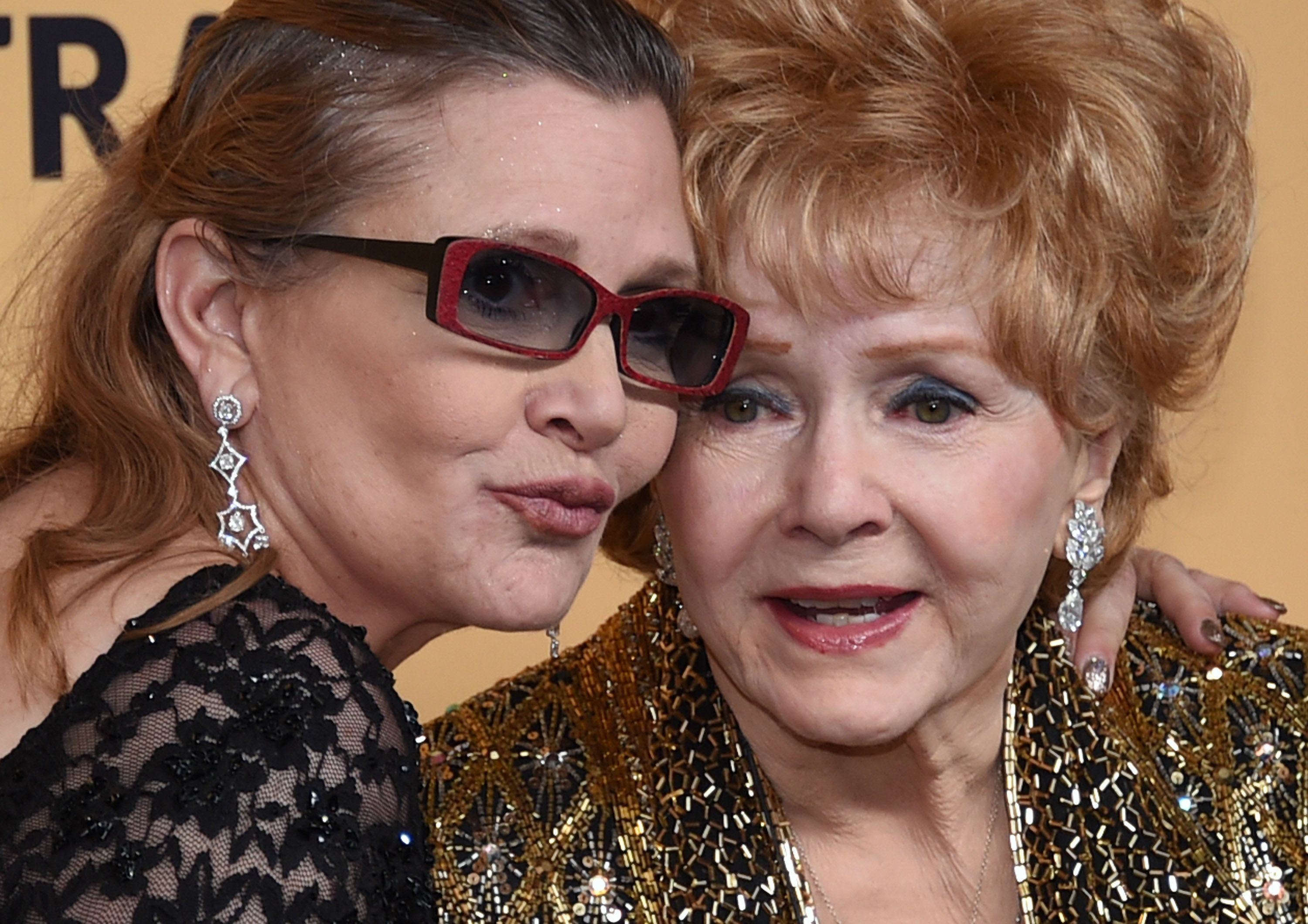 LOS ANGELES, CA - JANUARY 25:  Actresses Debbie Reynolds (R), recipient of the Screen Actors Guild Life Achievement Award, and her daughter Carrie Fisher pose in the press room during the 21st Annual Screen Actors Guild Awards at The Shrine Auditorium on January 25, 2015 in Los Angeles, California.  (Photo by Ethan Miller/Getty Images)