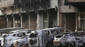 A gendarme inspects burnt-out vehicles outside the Splendid Hotel in Ouagadougou, Burkina Faso, January 16, 2016, after security forces retook the hotel from al Qaeda fighters who seized it in an assault that killed two dozen people from at least 18 countries and marked a major escalation of Islamist militancy in West Africa.  REUTERS/Joe Penney
