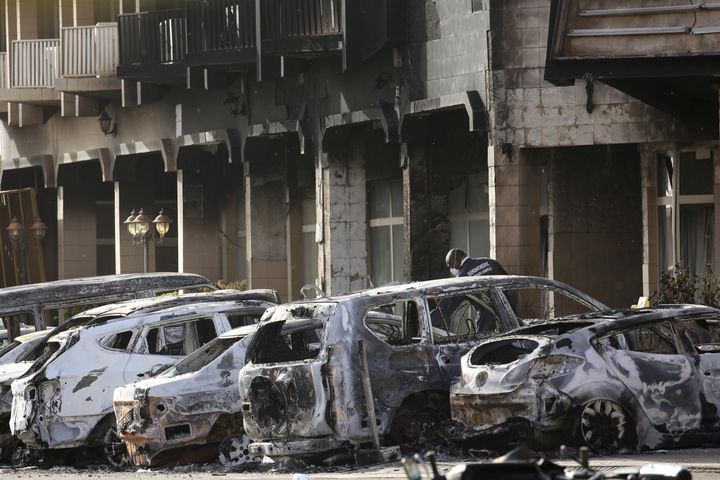 A gendarme inspects burnt-out vehicles outside the Splendid Hotel in Ouagadougou, Burkina Faso, on Jan. 16.