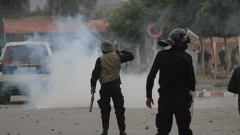 KASSARINE, TUNISIA - JANUARY 21: Riot police intervene to the protesters during a protest, staged by unemployed young citizens against unemployment and poverty in Kassarine, Tunisia on January 21, 2016. Protests against unemployment and poverty spread along the country, has been started on 19th of January in Kassarine, Tunisia. (Photo by Yassine Gaidi/Anadolu Agency/Getty Images)