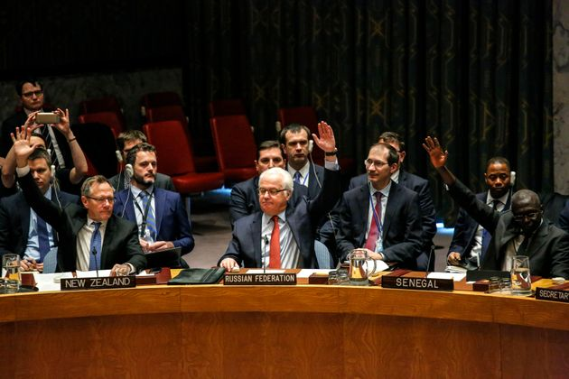 Russian Ambassador to the UN Vitaly Churkin (C) votes at the Security Council on a Russian-Turkish peace...