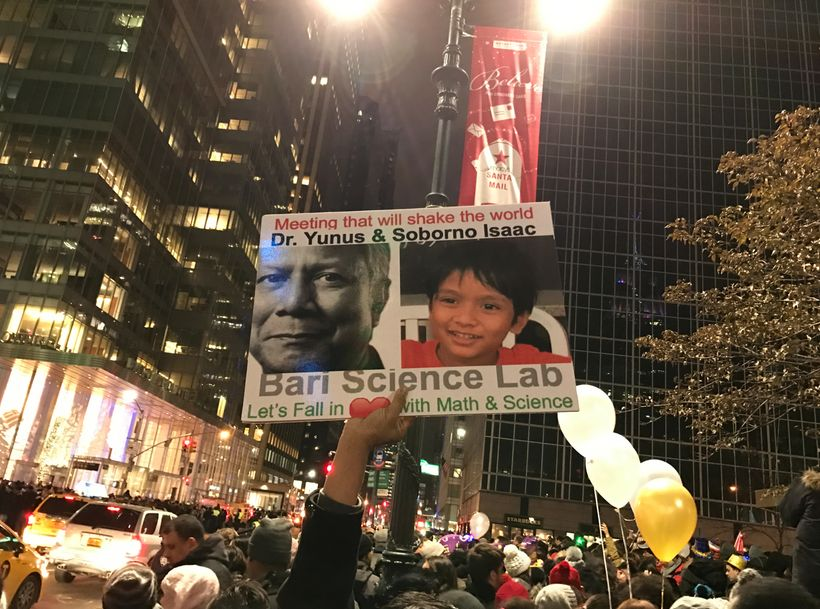 A fan of Isaac holds up poster at Times Square before New Year Celebration to promote the upcoming meeting between Nobel Laur