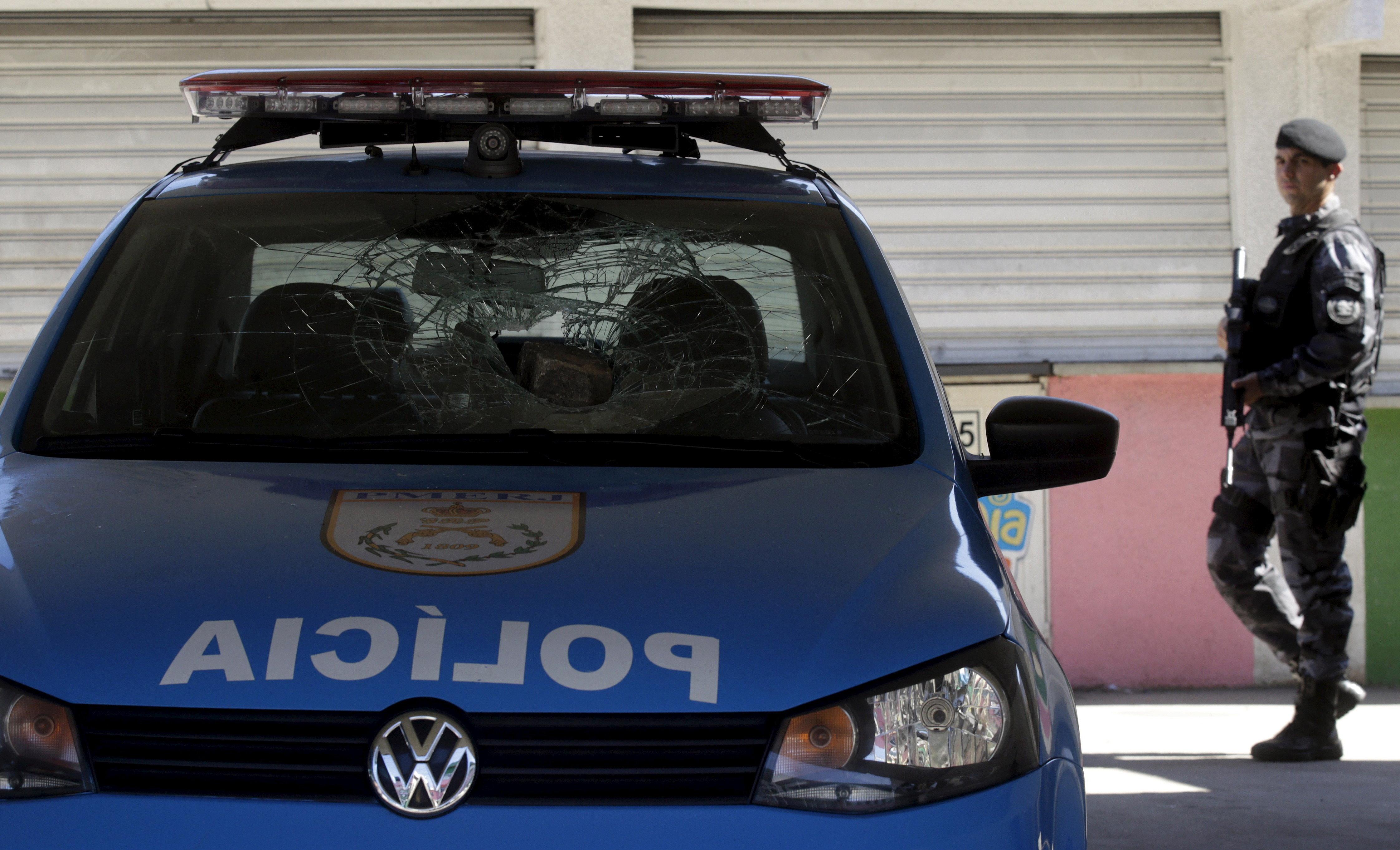 A policeman walks past a police car damaged during a protest at the Mangueira slum in Rio de Janeiro,...
