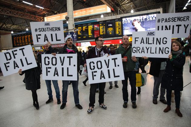 Demonstrators holding placards stage a protest at Victoria Station in