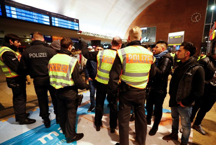 Police officers of Germany's federal police Bundespolizei check young men at the main railways station following New Year cel