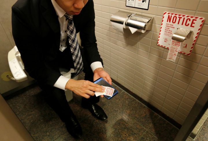 A man demonstrates the new cellphone toilet paper.