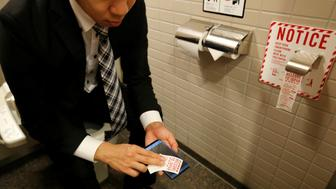 A man demonstrates a toilet roll for wiping smartphones, installed by Japanese mobile phone company NTT Docomo, in a high-tech bathroom equipped with bidet and heated seat at Narita international airport in Narita, Japan, December 28, 2016. REUTERS/Toru Hanai