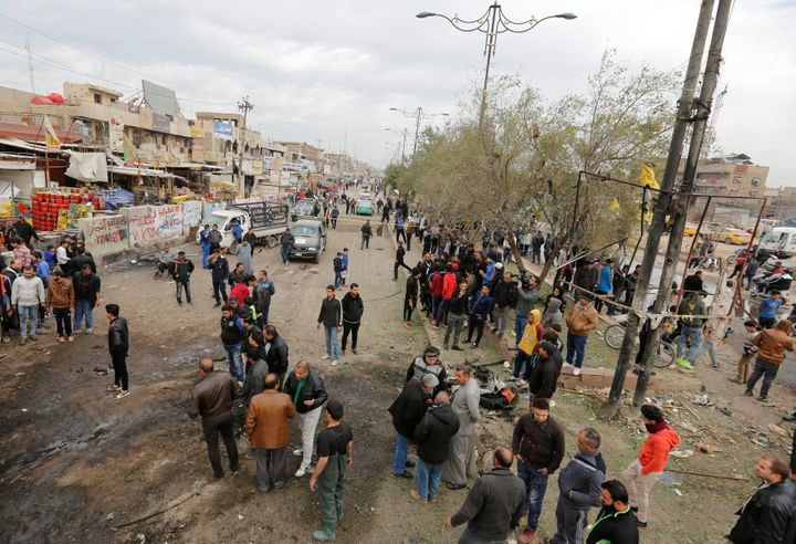 People gather at the site of car bomb attack in a busy square at Baghdad's sprawling Sadr City district, in Iraq January 2, 2