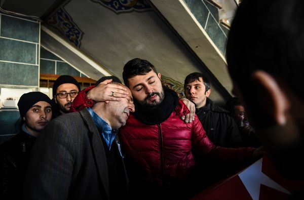 The father (L) and brother (R) of Yunus Gormek, 23, one of the victims of the Reina attack, mourn during his funeral ceremony