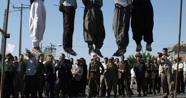Iranians watch the hanging of a convicted man in 2011. Iran has executed at least 73 young offenders...