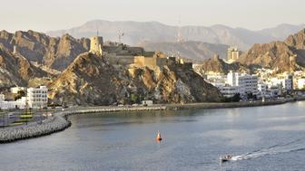 Hilltop fort on rocky outcrop overlooking the Muttrah Corniche and harbour in Muscat Oman