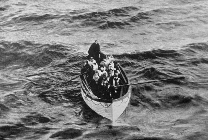 An emergency cutter lifeboat carrying a few survivors from the Titanic is seen floating near the rescue ship Carpathia on the