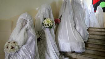 Brides wait for their grooms before a mass wedding ceremony in Amman July 6, 2012. An Islamic charity organized a mass wedding for 46 Jordanian and Syrian couples who are unable to afford expensive ceremonies. REUTERS/Ali Jarekji (JORDAN - Tags: SOCIETY)