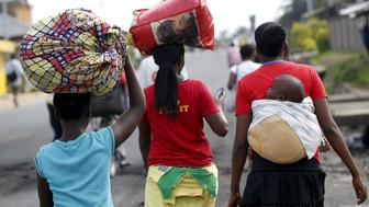 Women carry their belongings as they flee in fear of recent clashes between riot policemen and protesters against the ruling CNDD-FDD party's decision to allow President Pierre Nkurunziza to run for a third five-year term in office, in Bujumbura, Burundi April 29, 2015. A top U.S. diplomat was heading to Burundi on Wednesday, seeking to halt escalating unrest triggered by President Pierre Nkurunziza's decision to seek a third term in office, a move protesters say is unconstitutional. REUTERS/Thomas Mukoya