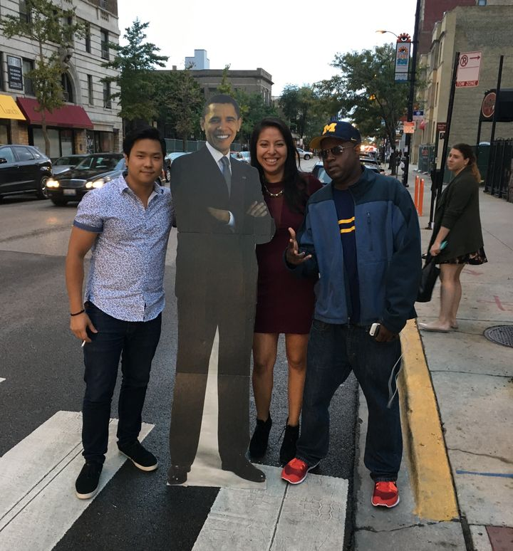 Three random strangers brought together by a cut-out of Barack Obama.