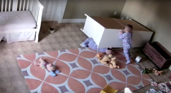The 2-year-old boy is seen pushing a dresser off of his twin brother after it toppled on him in their bedroom last week.