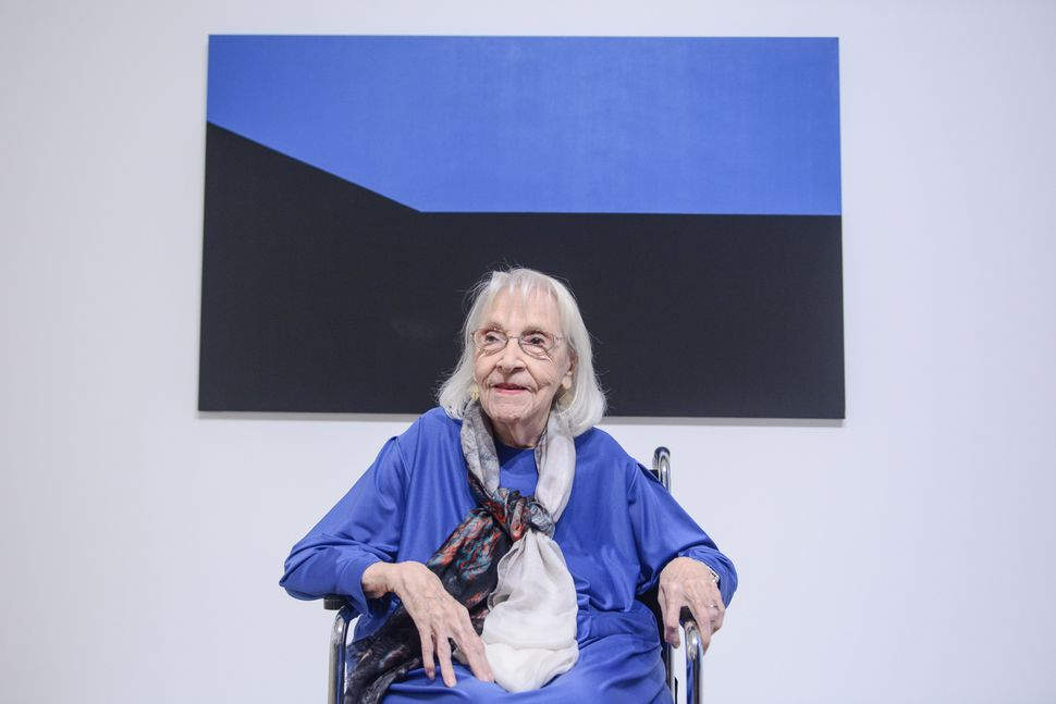 "Portrait of Carmen Herrera in front of Blue Monday, 1975, acrylic on canvas, as installed in ""Carmen Herrera: Lines of Sight"""
