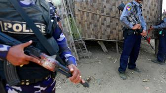 Police stand guard as the government embarks on a national census at a Rohingya village in Sittwe March 30, 2014. The government on Sunday embarked on its first national census in more than 30 years. REUTERS/Soe Zeya Tun (MYANMAR - Tags: POLITICS)
