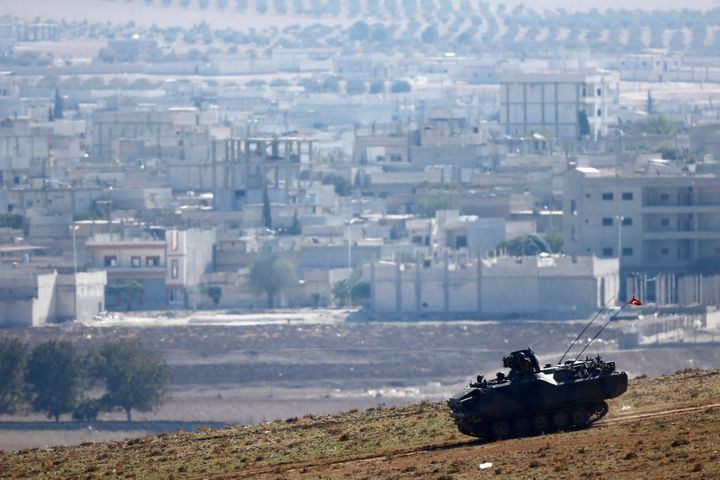 A Turkish army tank drives downhill, in front of ruins of the Syrian town of Kobani (seen in the background) near the Mursitp