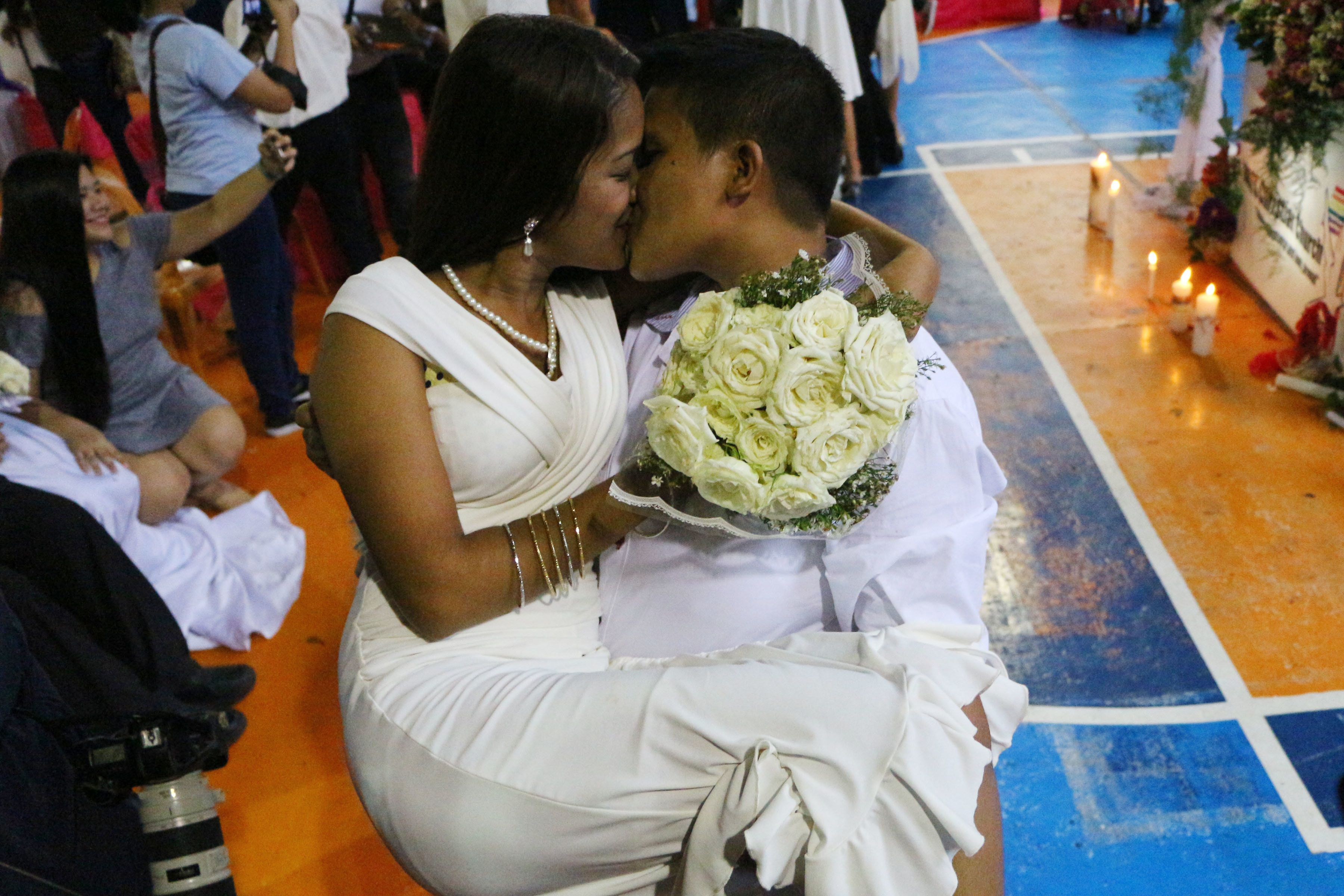 PHILIPPINES - 2016/06/26: Filipino LGBT (Lesbian, Gay, Bisexual and Transgender) couples Mercy Tuibeo, 32 yrs old (right) carry Virgie Icawat, 20 yrs old (left) and kiss each other during the wedding  each after the mass wedding officiated by Rev. CJ Agbayani Jr. of LGBT Christian Church at Mendoza Covered Court in Brgy. Pinalabanan. (Photo by Gregorio B. Dantes Jr./Pacific Press/LightRocket via Getty Images)