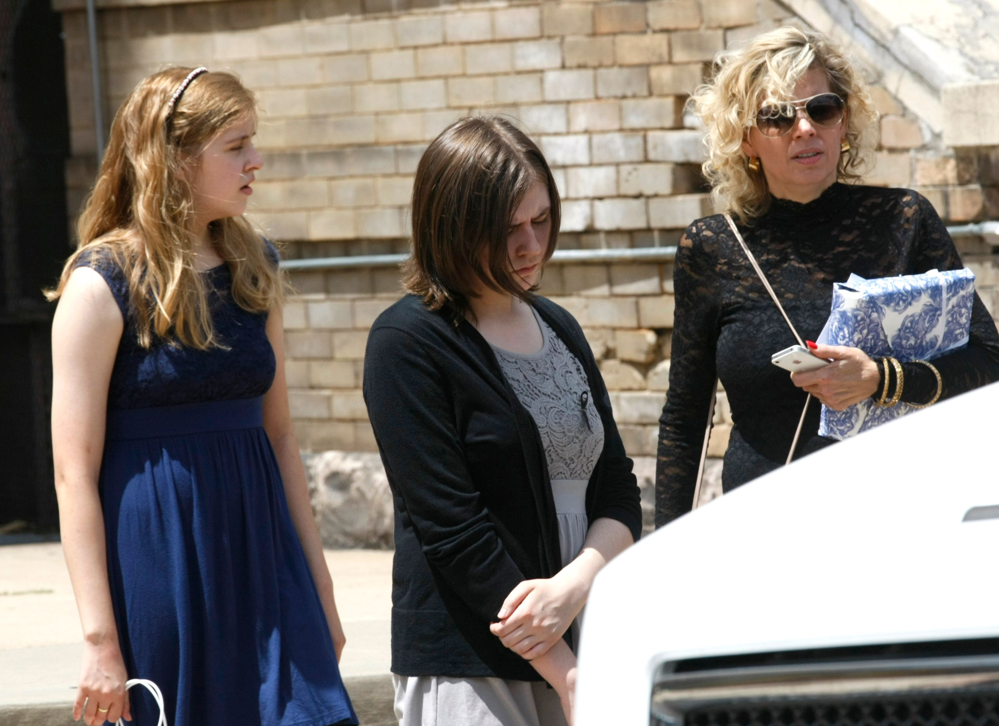 "Two daughters of Gordon Cowden and his ex-wife (R) leave his memorial service at Pathways church in Denver July 25, 2012. The man accused of the shooting rampage in a Denver-area screening of the latest ""Batman"" movie mailed a notebook detailing his plans to a psychiatrist days before the attack, FoxNews.com reported on Wednesday. Cowden, along with 11 others, was killed at a movie theater in Aurora, Colorado last Friday. The daughters are Kristian, Brooke and Cierra.  REUTERS/Rick Wilking (UNITED STATES - Tags: DISASTER POLITICS CRIME LAW)"