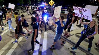 Charlotte-Mecklenburg police officers watch as protesters walk through Charlotte, N.C., on Saturday, Aug. 22, 2015. Protesters marched on Friday evening and Saturday, protesting that after four days of deliberations, a mistrial was declared when the jury was unable to resolve a deadlock in the case of Randall 'Wes' Kerrick. Kerrick, a Charlotte-Mecklenburg police officer, is accused of killing an unarmed man, Jonathan Ferrell, in a struggle two years ago. (Jeff Siner/Charlotte Observer/TNS via Getty Images)
