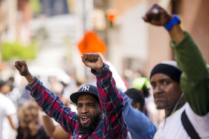 Pedestrians gesture as a march passes by on the way to a rally at Baltimore city hall in Baltimore, Maryland May 2, 2015. A j