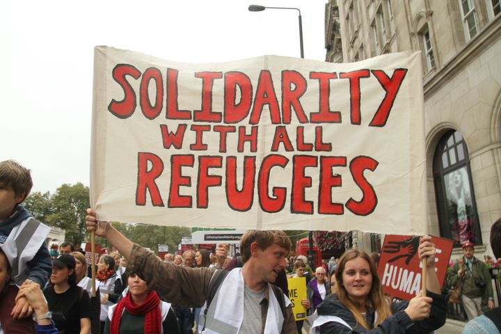 LONDON, UK - September 17: Demonstrators carry a banner during ​thr Refegees Welcome march through London to show solidarity