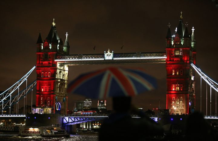 A man shelters from the rain beneath a Union flag-themed umbrella as he photographs London's iconic Tower Bridge, illuminated