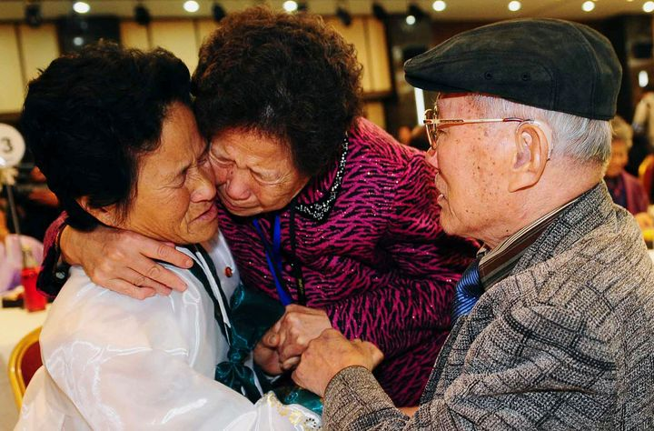 South Korean Kim Sung-bok (R), 90, with an unidentified South Korean family member, meets his daughter Kim Hee-sook (L), 61,
