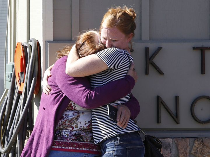 Umpqua Community College alumnus Donice Smith (L) is embraced after she said one of her former teachers was shot dead, near t