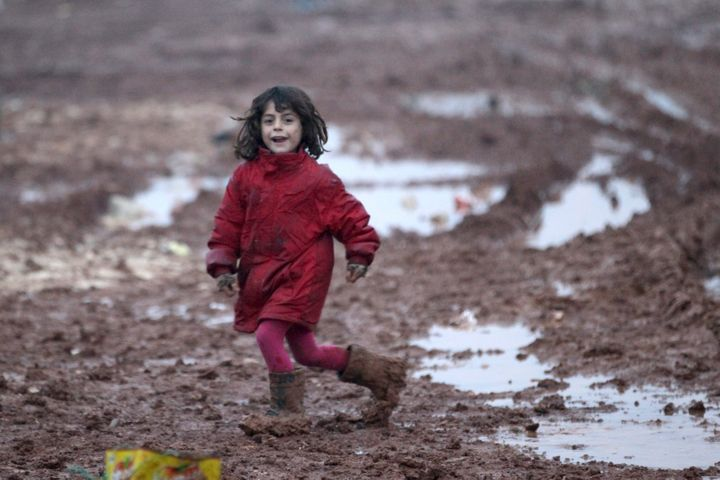 An internally displaced Syrian girl runs through mud in the Bab Al-Salam refugee camp, near the Syrian-Turkish border, northe