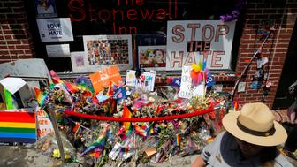 A member of the National Park Service walks by a memorial to the victims of the Orlando Pulse shooting outside The Stonewall Inn following a ceremony officially designating The Stonewall Inn and Christopher Park as a national monument in the Manhattan borough of New York, U.S., June 27, 2016.  REUTERS/Andrew Kelly