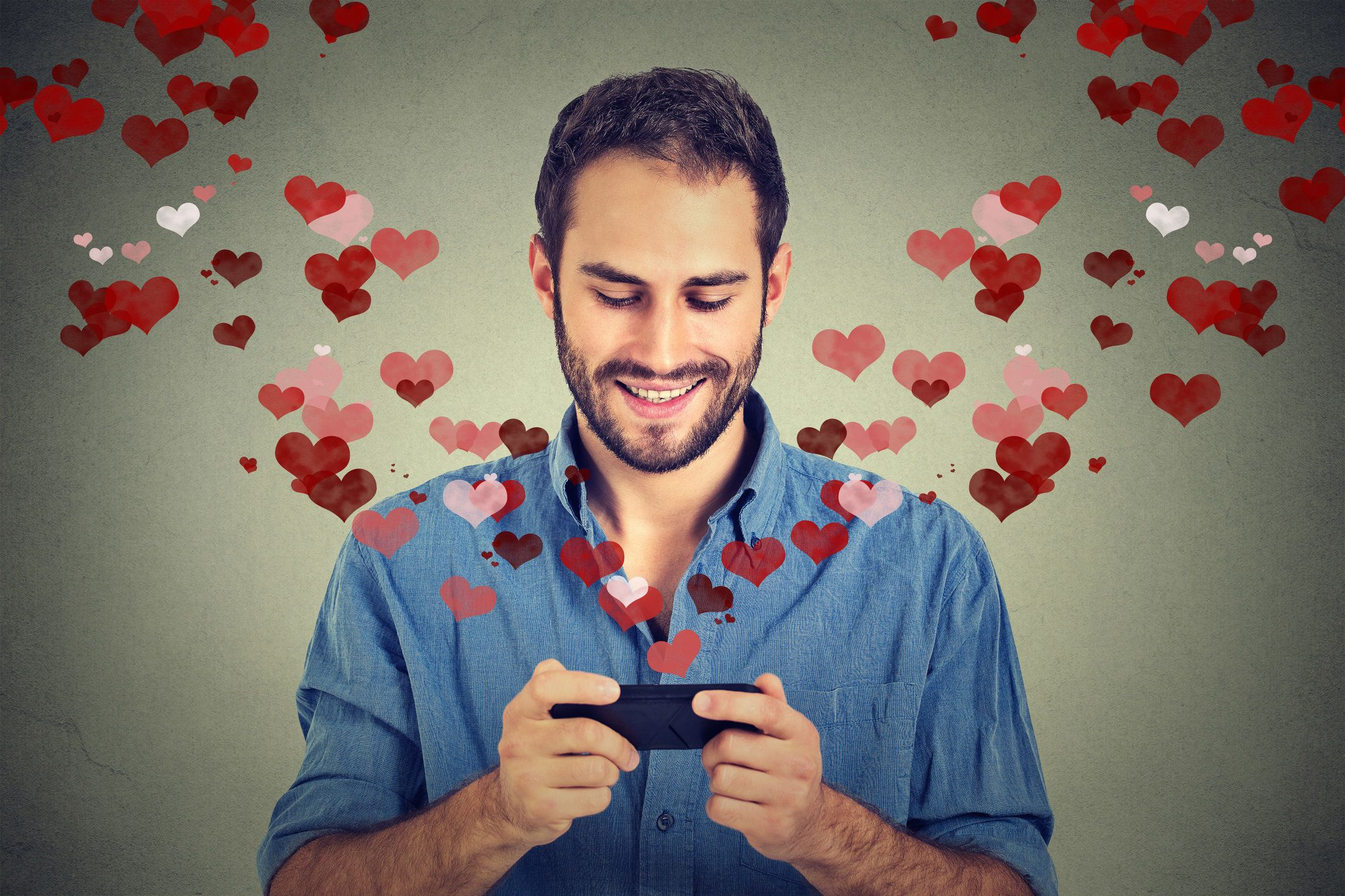 Portrait happy man sending love sms text message on mobile phone with red hearts flying away from screen isolated on grey wall background. Human emotions