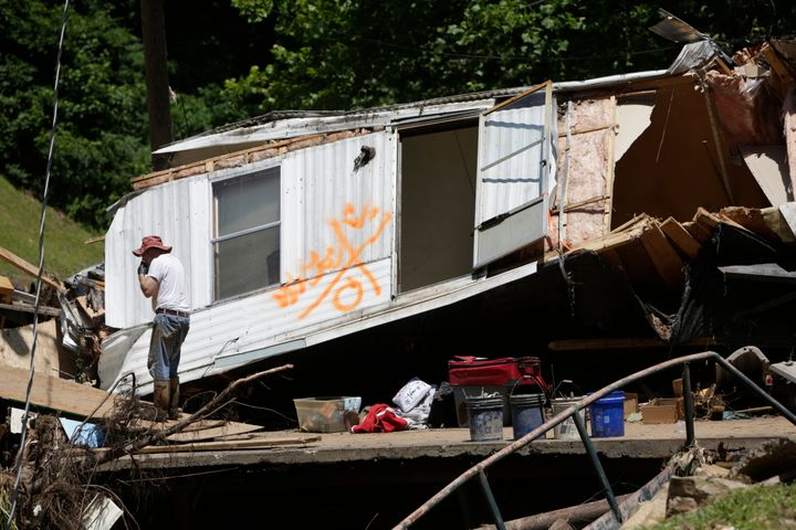 Maynard Tanner, 65, eats a snack on a damaged bridge as part of a mobile home that floated down Jordan Creek rests behind him